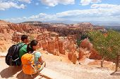 Hikers in Bryce Canyon resting enjoying view Hiking couple in beautiful nature landscape with hoodoo