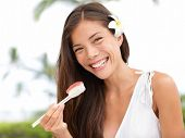 Woman eating sushi outside in summer dress smiling happy at camera. Mixed race Asian Caucasian girl eating healthy fresh food.