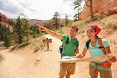 People hiking looking at hike map in Bryce Canyon. Young multiracial couple of hikers navigating and smiling happy during hike in Bryce Canyon National Park landscape, Utah, USA. Young woman and man.
