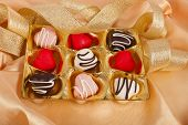 chocolate and marzipan hearts candies on golden silk textured cloth background