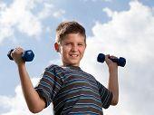 Niño levantando pesas al aire libre