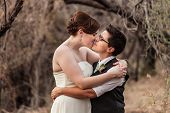 image of same sex  - Happy same sex newlyweds kissing in the woods - JPG