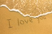 I love you - inscription on the beach sand, soft surf wave.