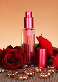 Women's perfume in beautiful bottle with rose on brown background
