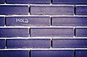 Spanish Hello 'hola'  Written On Brick To Wall