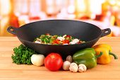 Wok with vegetable ragout on wooden table, on bright background