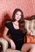Beautiful Smiling Girl In Short Black Dress With Handbag Sits On Vintage Couch.