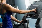 woman adjusts the treadmill