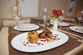 Grilled rack of lamb with potatoes and vegetables on restaurant table