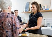 stock photo of over counter  - Senior woman paying through smartphone over electronic reader at cafe counter - JPG