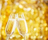 Two glasses of champagne with lights in the background. very shallow depth of field, , focus on near glass.