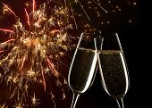 New Year's concept.   Celebration on New Year's Eve.    in the  background fireworks. Close up of two glasses of Champagne clinking together.