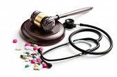 judge's gavel with stethoscope and pills on white background