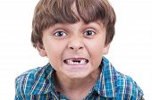 stock photo of missing teeth  - Closeup of cute little boy showing mouth of missing front teeth on white background - JPG