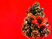 Christmas tree made with pinecones foreground on red background