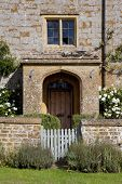 stock photo of english cottage garden  - Stone farmhouse doorway with white roses and garden gate - JPG