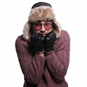 young man dressed in winter clothes and warm fur hat is  scared about the cold of winter on white ba