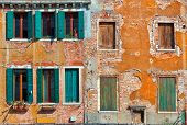 Facade of typical old colorful house with small windows, wooden shutters and cracked brick wall in Venice, Italy.