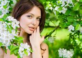 Portrait of young woman touches her face standing near the flowered tree in the park. Concept of you