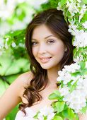 stock photo of nearly nude  - Portrait of young woman near the blossomed tree in the park - JPG
