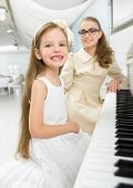 Master teaches little girl to play piano. Concept of music study and art