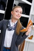 Woman with shoe in hand chooses stylish shoes looking at the shelves with numerous pumps