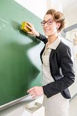 Teacher or docent cleaning the chalk of the board or  chalkboard or blackboard after the math lesson