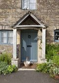 stock photo of english cottage garden  - Pretty Cotswold cottage doorway with basket and flowers - JPG