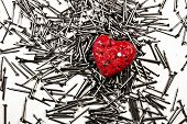 Red Heart On Pile Of Iron Nails, Pierced By A Nail And Holes In It