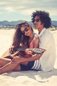 stock photo of serenade  - Cute hispanic couple playing guitar serenading on beach in love and embrace - JPG