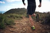 pic of crossed legs  - trail running athlete exercising for fitness and health outdoors on mountain pathway - JPG