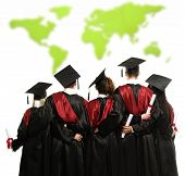Group of graduated young students in black mantles against world map