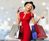 Smiling young blond woman with shopping bags in shop interior