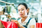 Seamstress or worker in a chinese factory sewing with a industrial sewing machine, she is very accurate