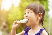 foto of popsicle  - happy little girl eating popsicle at summertime with sunset - JPG