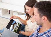 Couple Sitting On Couch Looking At Picture Of Real Estate