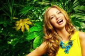 Beautiful laughing young woman among the tropical plants. Vacation. Tropics. Fashion shot.