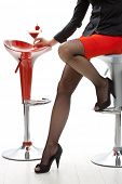 Sexy female legs in black high heels and fishnet stockings, red mini skirt. Holding cocktail drink i
