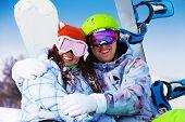 Smiling couple in ski mask sitting hugging