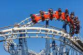 Roller coaster ride under blue sky.