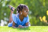 Outdoor Portrait Of A Cute Young Black Girl  Lying Down On The Grass - African People