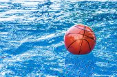 image of netball  - dirty basketball on the water of swimming pool in outdoor lighting - JPG