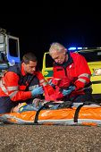 Paramedic team giving first-aid to injured woman at night