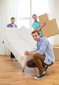 moving, real estate and friendship concept - smiling male friends with sofa and boxes at new home