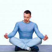 Concentrated sportsman sitting in the lotus position on gray background