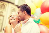 summer holidays, celebration and dating concept - happy couple with colorful balloons in the city