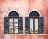 Wall with two old arched windows with shutters, rustic texture