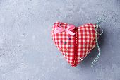 Fabric heart with color pins on color wooden background