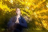 pic of namaste  - Casual dressed young man looking at camera with namaste greeting in autumn park - JPG