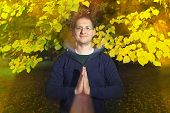image of namaste  - Casual dressed young man looking at camera with namaste greeting in autumn park - JPG